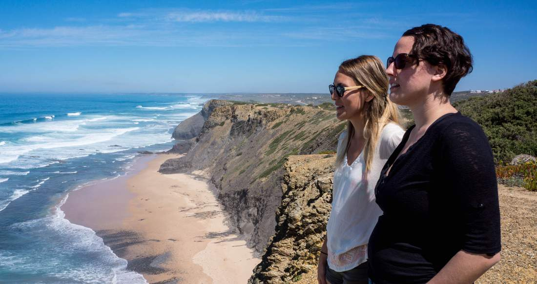 Two girls lookout from the top of a large cliff at a beautiful beach and open ocean