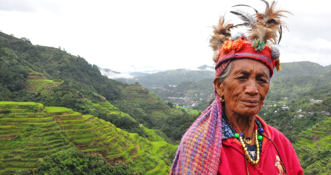 Tribe woman standing in front of the banaue rice terraces in the Philippines