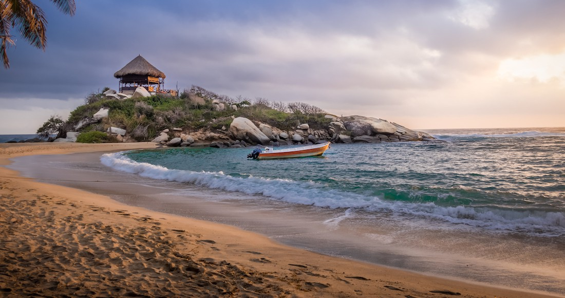 A boat floats in a small bay along a beautiful beach at sunset