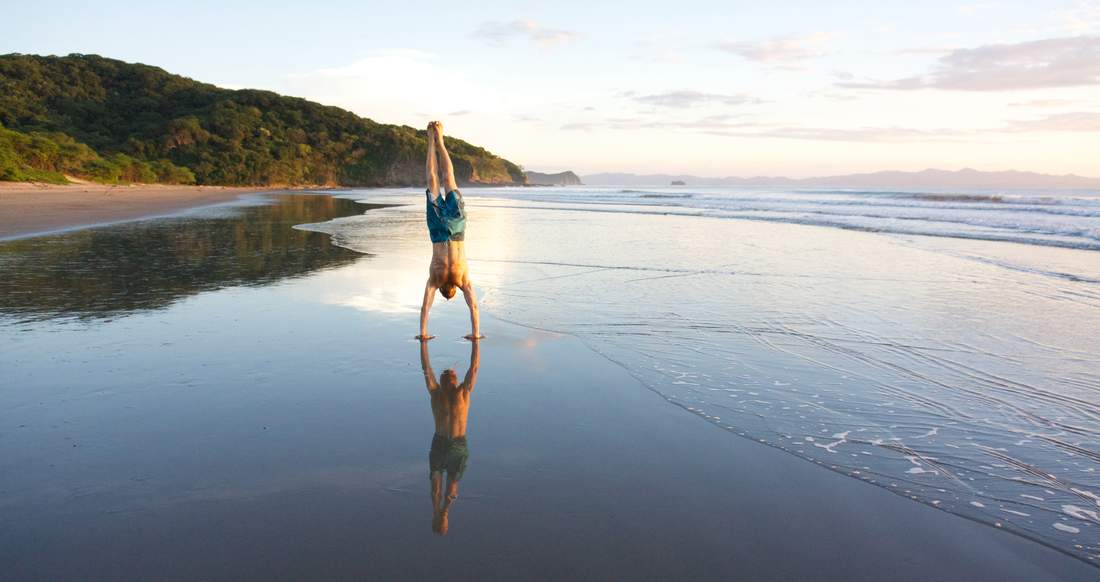 A man does a hand stand on a beautiful beach