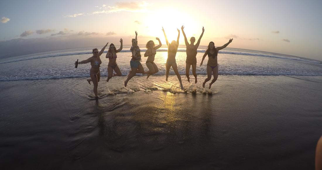 A group of people do a jumping pose on a beach at sunset
