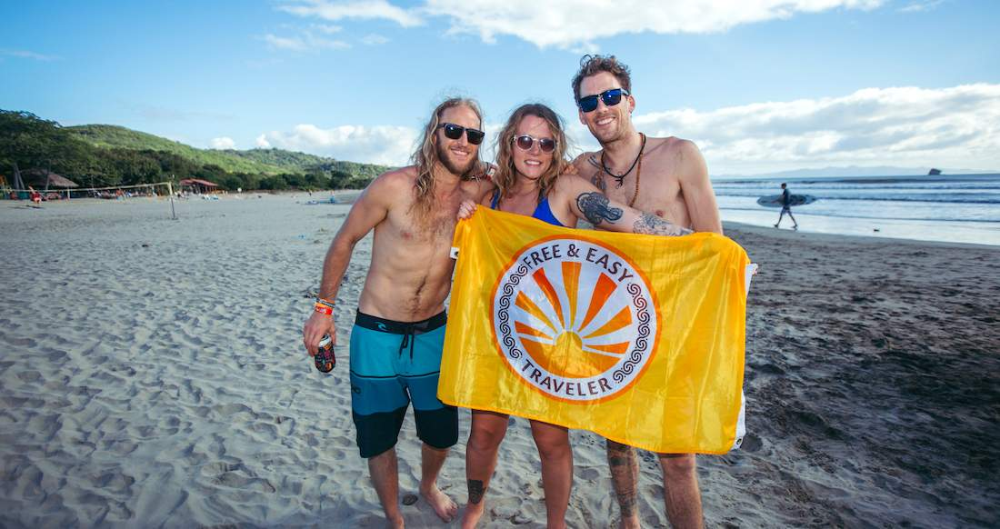 A girl and two guys pose on a beach holding a bright yellow flag as a s surfer walks in the distance