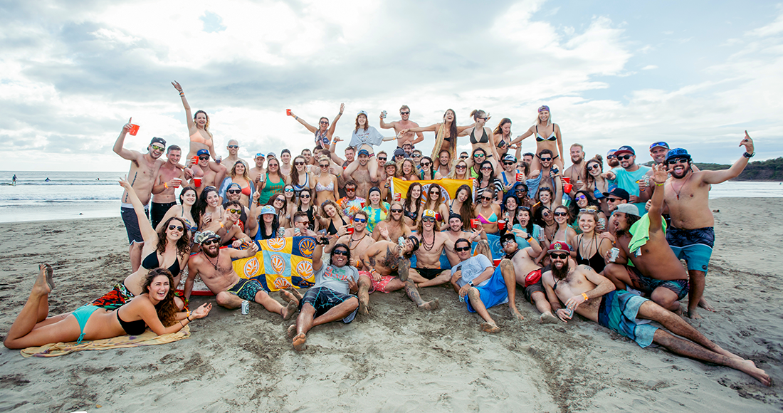 A large group of smiling people pose for a photo on a beautiful beach