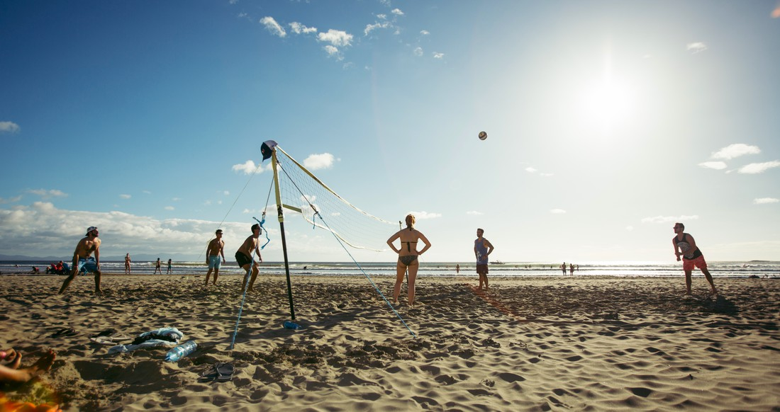 A group of people play beach volleyball on a white sandy beach