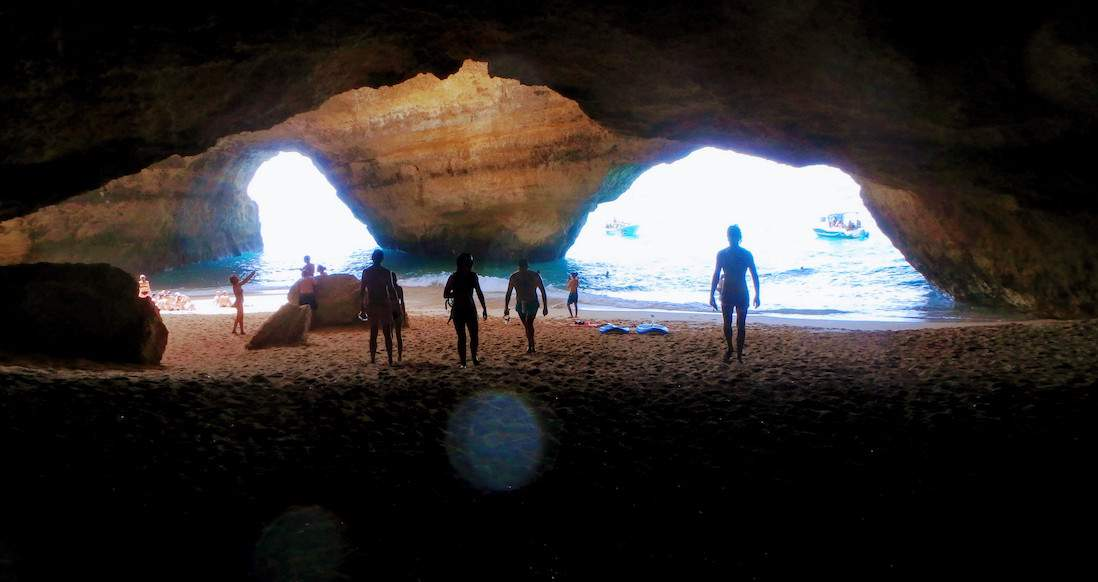 silhouettes of people standing inside a cave look at the ocean through two large rock openings