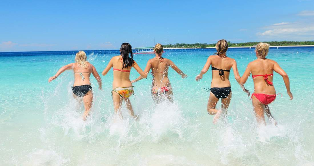 Girls running into crystal blue water in Indonesia