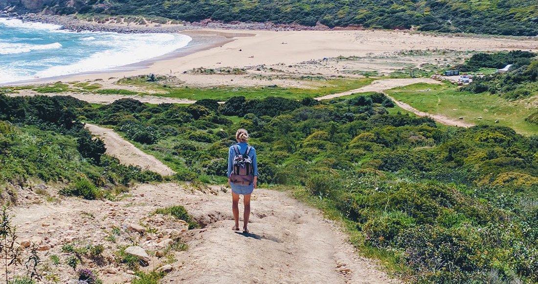 A traveler walks down to an empty beach