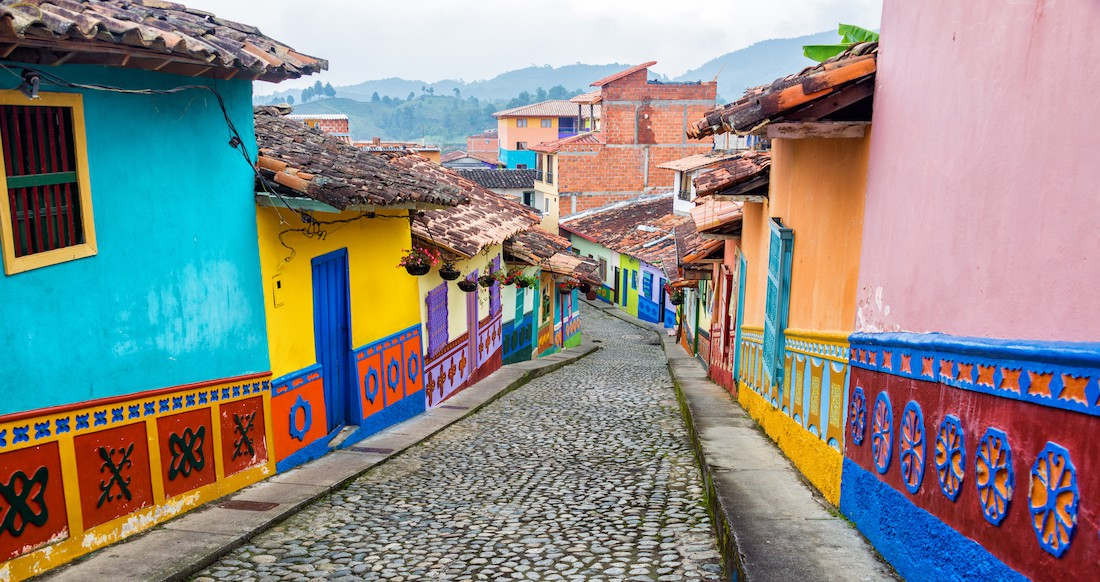 Colourful buildings line a cobblestone road with mountains in the background