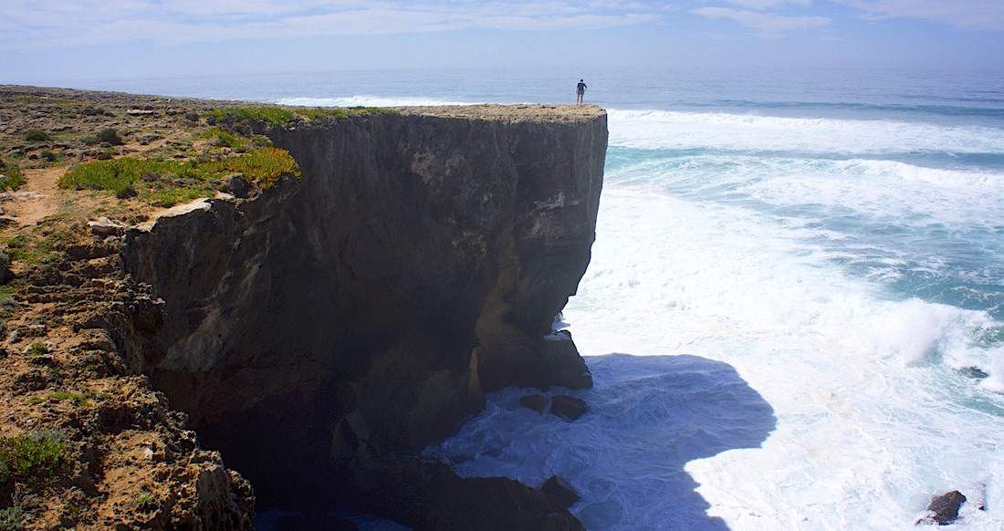 Person stands at edge of large cliff overlooking waves on the ocean