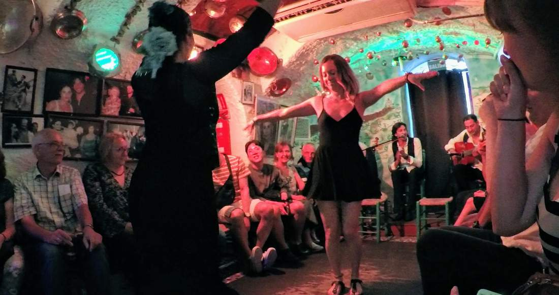 A girl gets Flamenco lessons in a small room surrounded by people