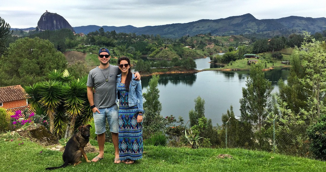 A couple stands with a dog in front of a beautiful lake surrounded by rolling green hills