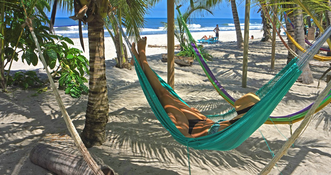 A women relaxes in a colourful hammock along a palm tree lined beach