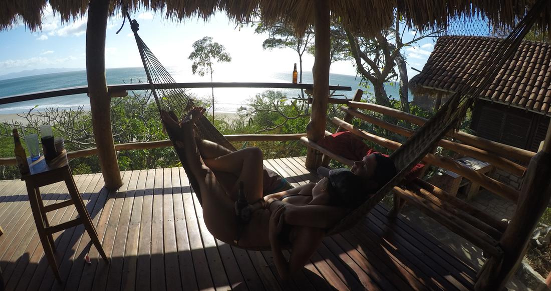A couple lounges in a hammock that overlooks the ocean