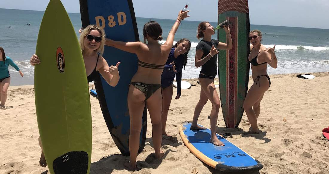 girls on kuta beach with their surfboards