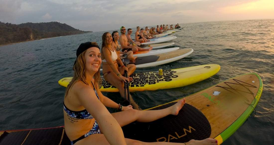 A group of people are lined up on Paddle boards in the ocean at sunset
