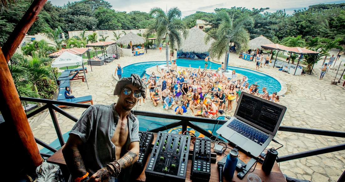 A Dj takes a selfie from a balcony with a group of people partying at a pool below