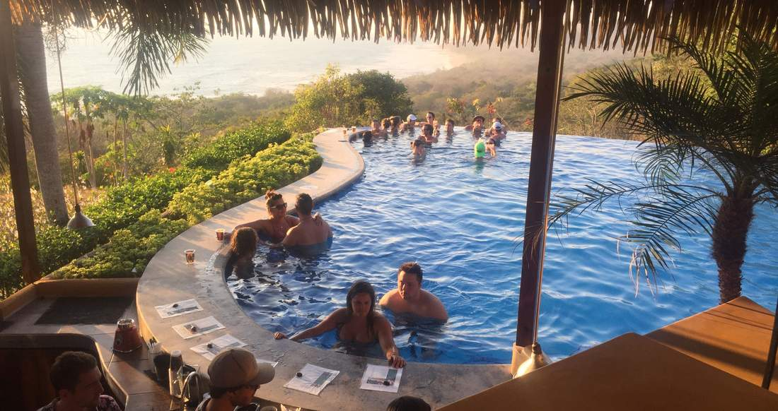 People swim up to a bar in a pool surrounded by lush jungle with a view of the ocean