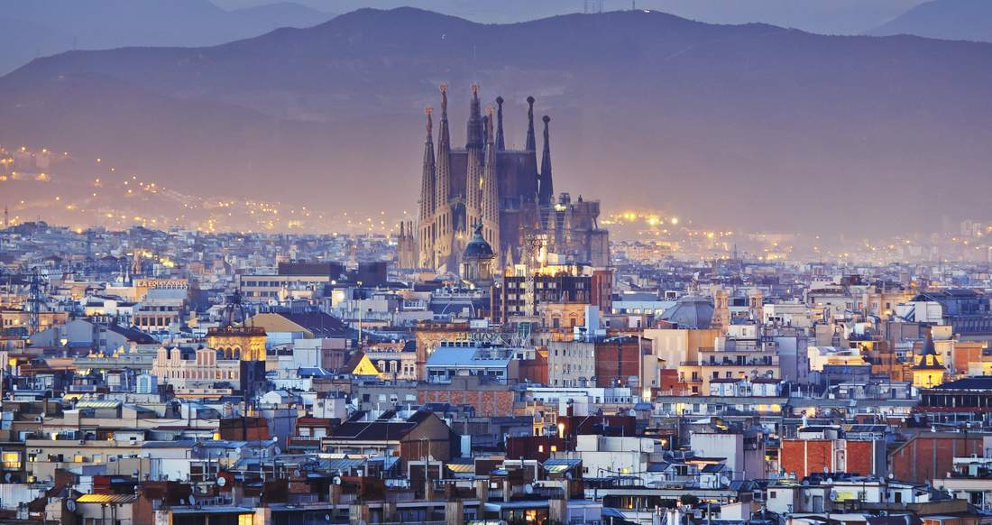 Sagrada Familia towering over the expansive city of Barcelona at dusk
