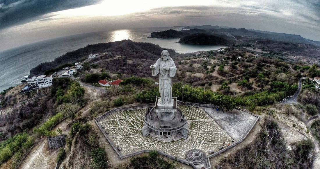 Aerial view of a large Jesus statue on a mountain with a view of the coastline and surrounding town