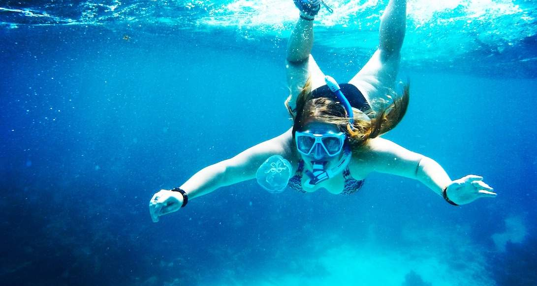 A girl gets close up to a jellyfish while snorkeling