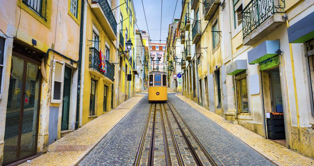A Streetcar drives down a narrow lane between cobblestone and colourful buildings