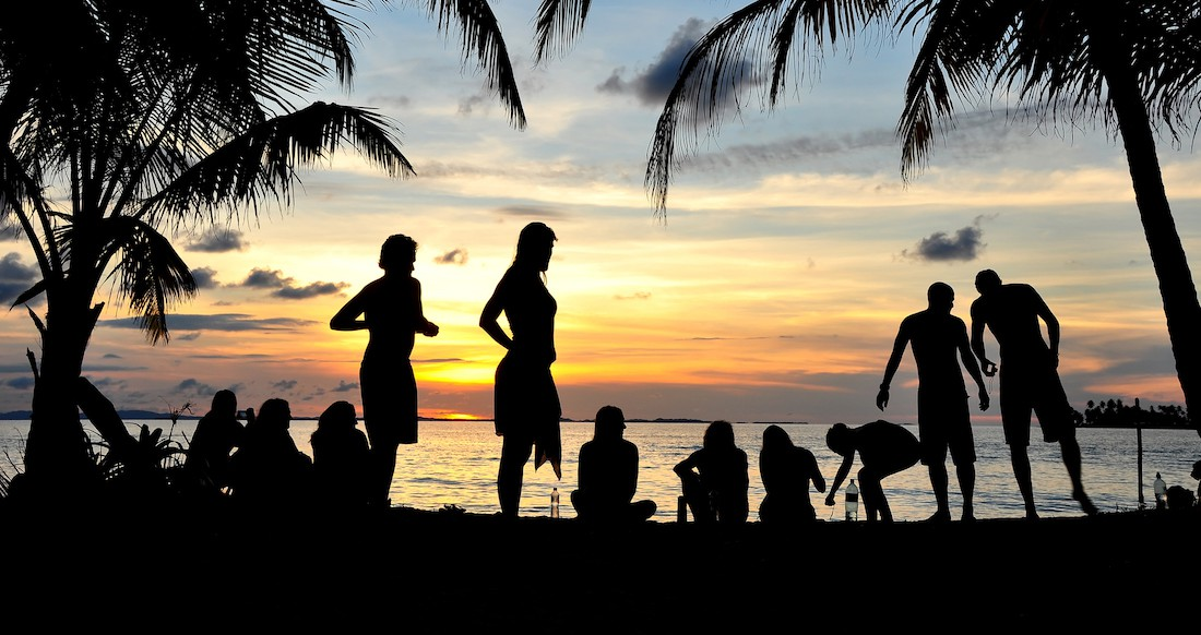 Silhouettes of people and palm trees on a beach at sunset