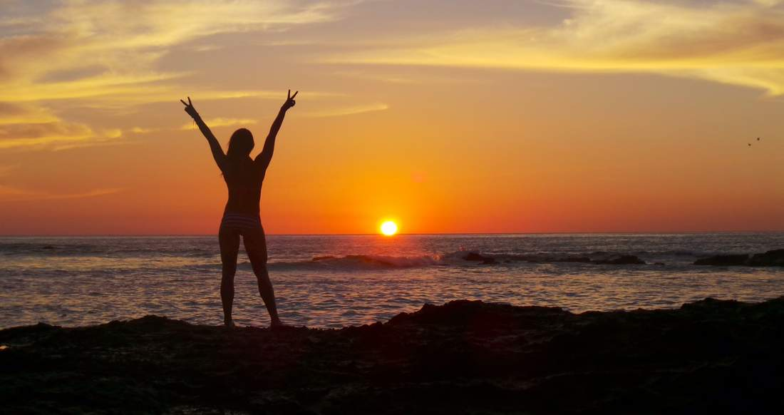 A Silhouette of a girl on a beach stretching out her arms giving the peace sign at sunset