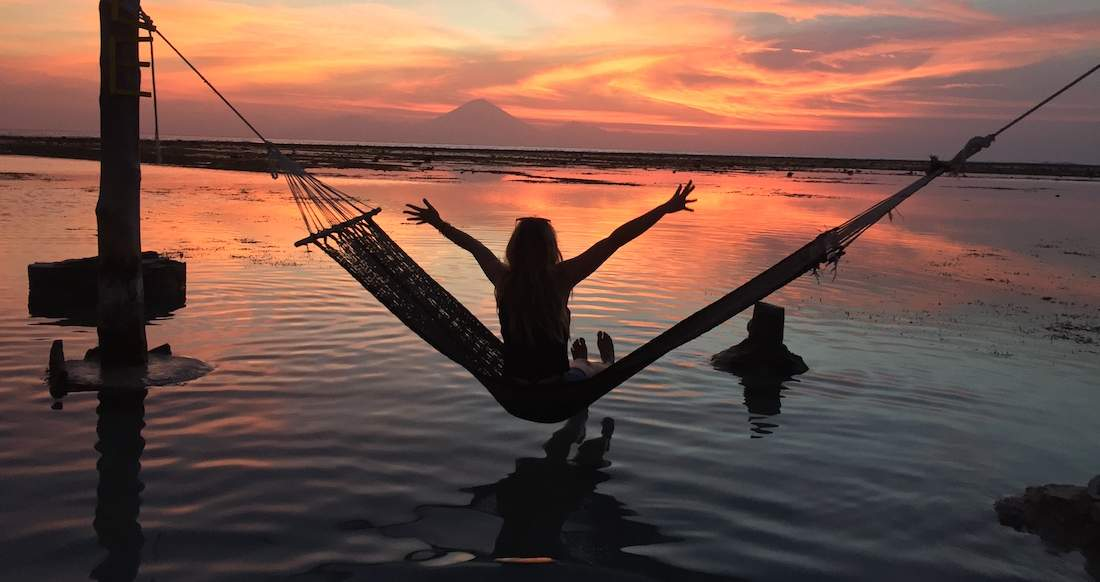 Girl watching beautiful sunset from a hammock in Indonesia