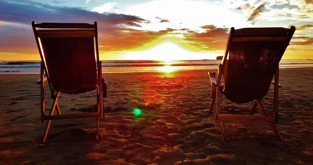 Two empty beach chairs stand on a quite beach while the sunsets over the ocean creating a deep orange sky