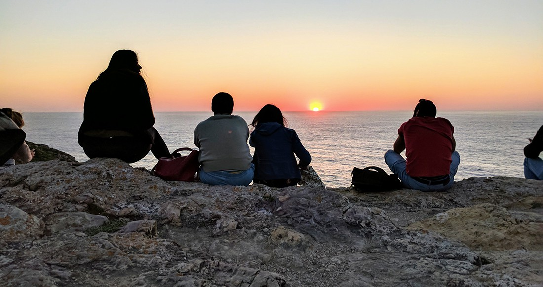 A group of travelers watch the sunset over the ocean