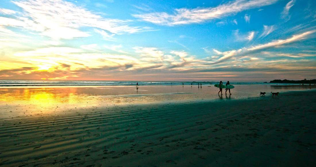 Surfers walk along an expansive beach at sunset