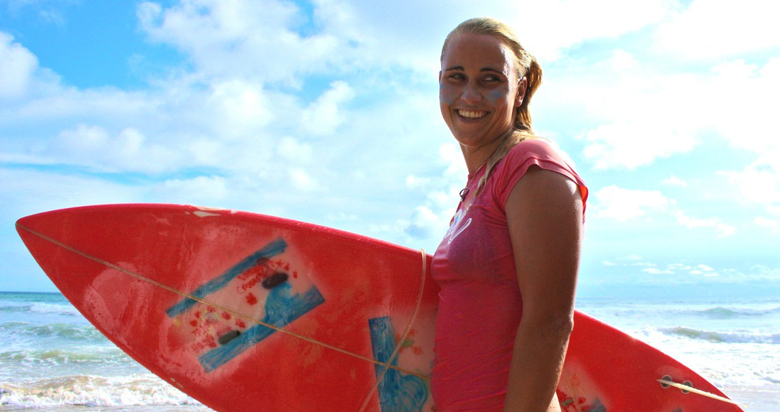 Close up of a girl smiling and holding a surfboard