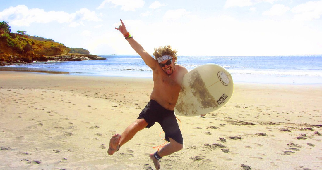 A man wearing a bandana jumps up in the air with his surf board