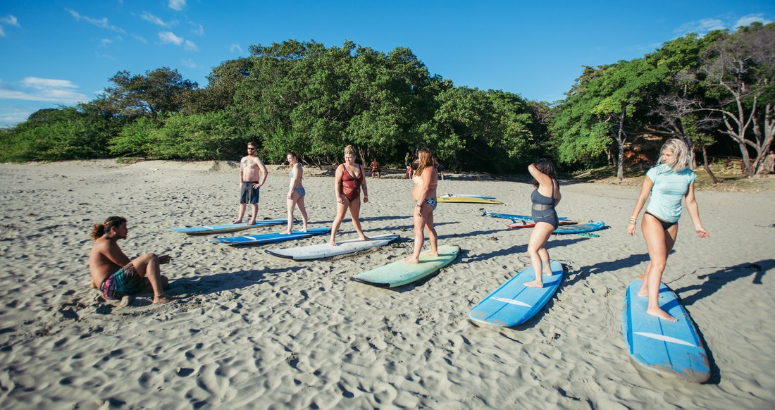 A group of people get surf lessons on a beach