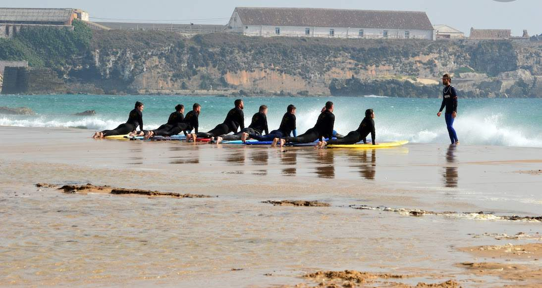 A group of people get surf lessons on brightly coloured surf boards