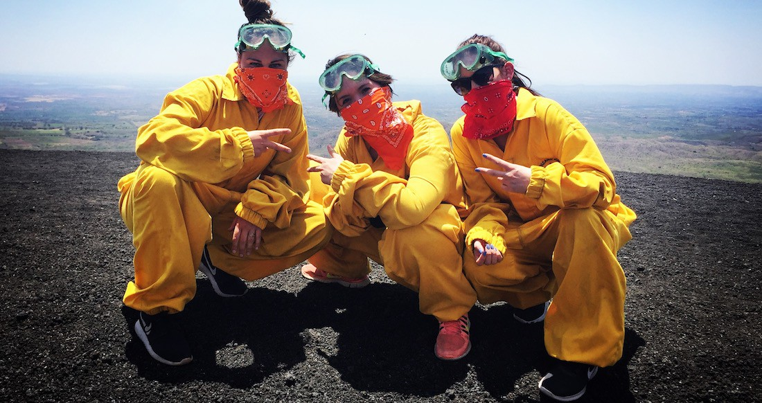 Three girls in yellow jumpsuits, green goggles, and orange handkerchiefs kneel on black volcanic sand on top of a steep hill