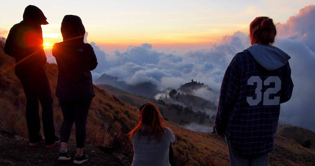 Group of people in warm clothing watching the sunrise over a volcanic crater