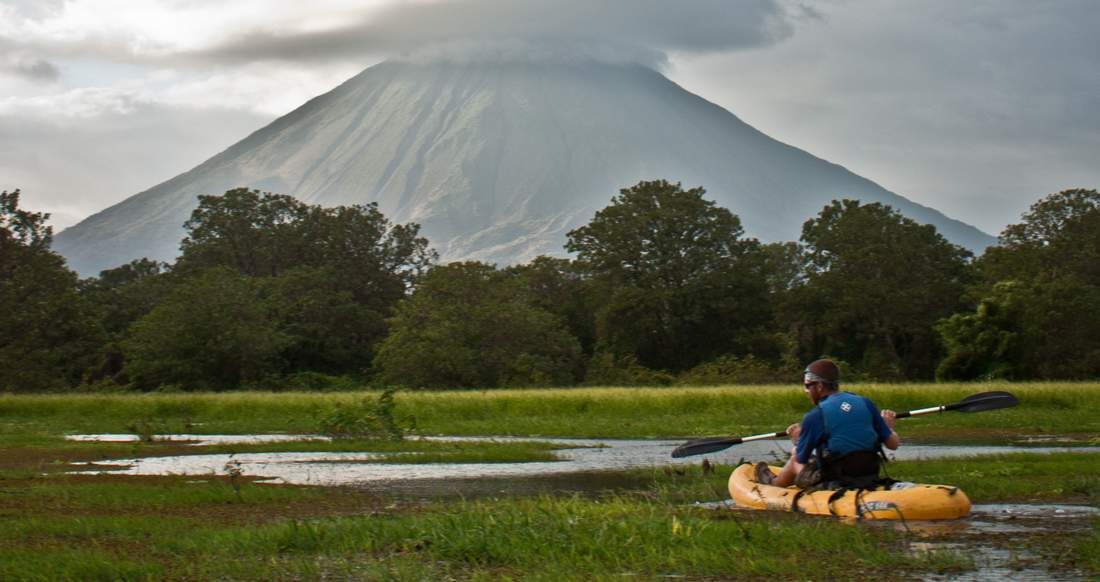 A man Kayaks through a marshy river with a large Volcano in the background