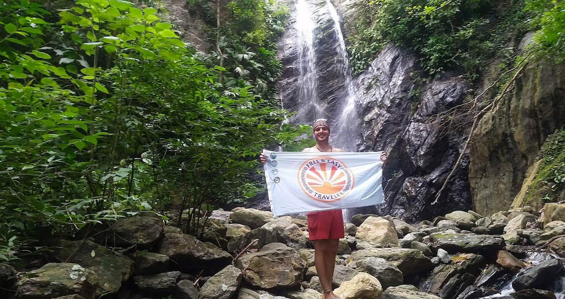 A man stands in front of a waterfall holding a blue flag that says Free and Easy Traveler on it.
