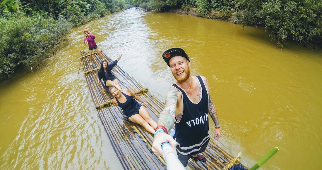 Group of travelers floating down a river on a bamboo raft in Northern Thailand