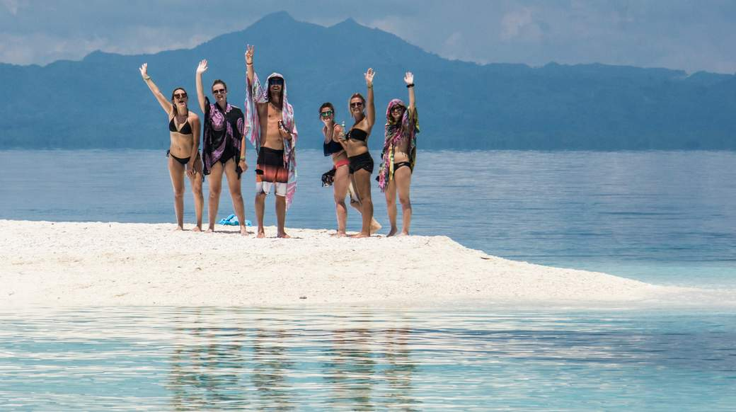 A group of travelers smiling on a white sand beach in the Philippines