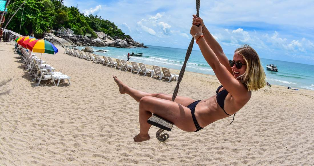 Traveler on a swing on a beach in Southern Thailand