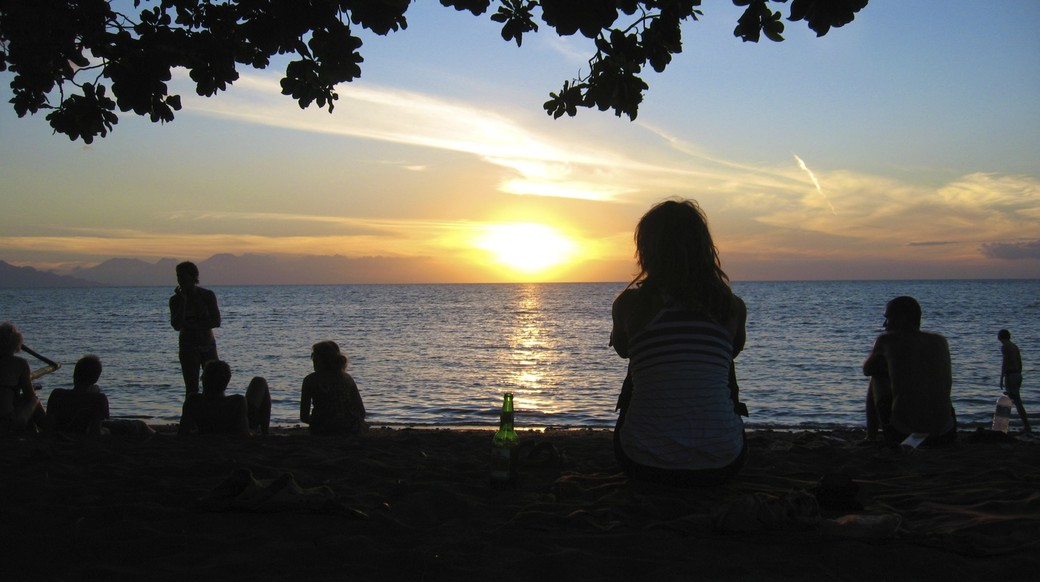 Travelers enjoying beer while watching the sun set on a beach in Indonesia