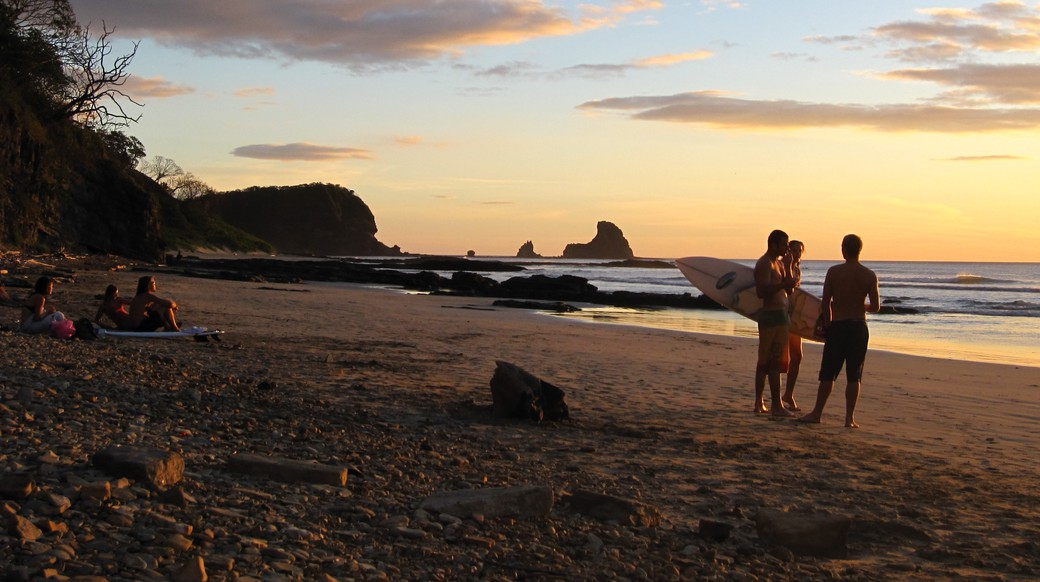 group of travelers on the beach with their surfboards while the sun sets in Nicaragua