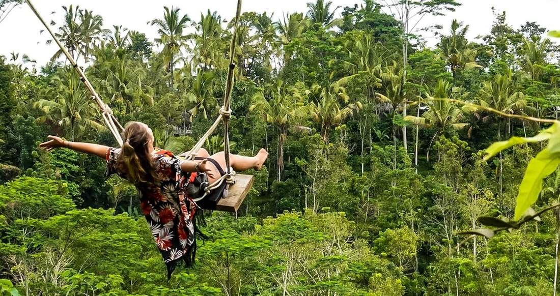 A girl holds her arms out joyfully as rides a swing over the jungle.