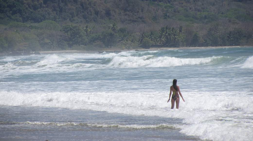girl standing in the ocean with big waves in Costa Rica