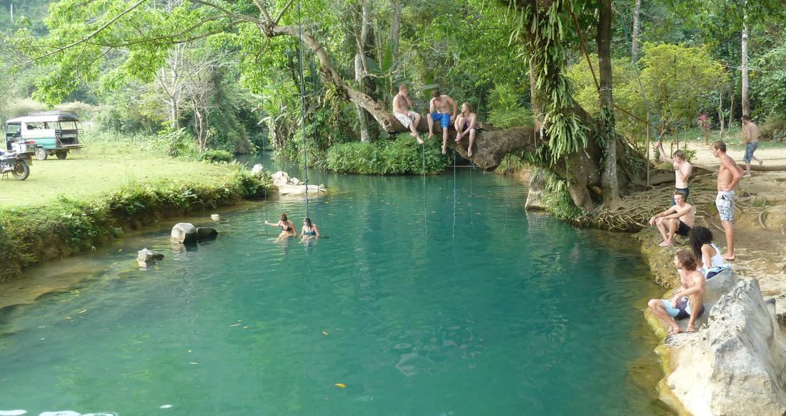 People hanging out around a river in Laos