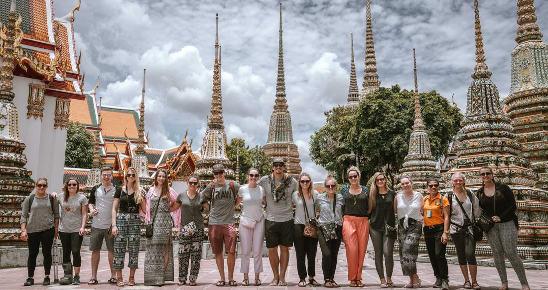 A group of travelers pose at a Thai temple.