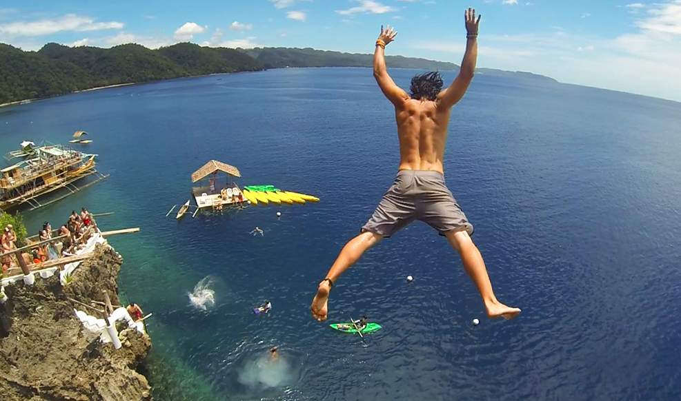 Traveler cliff jumping into the ocean in the Philippines