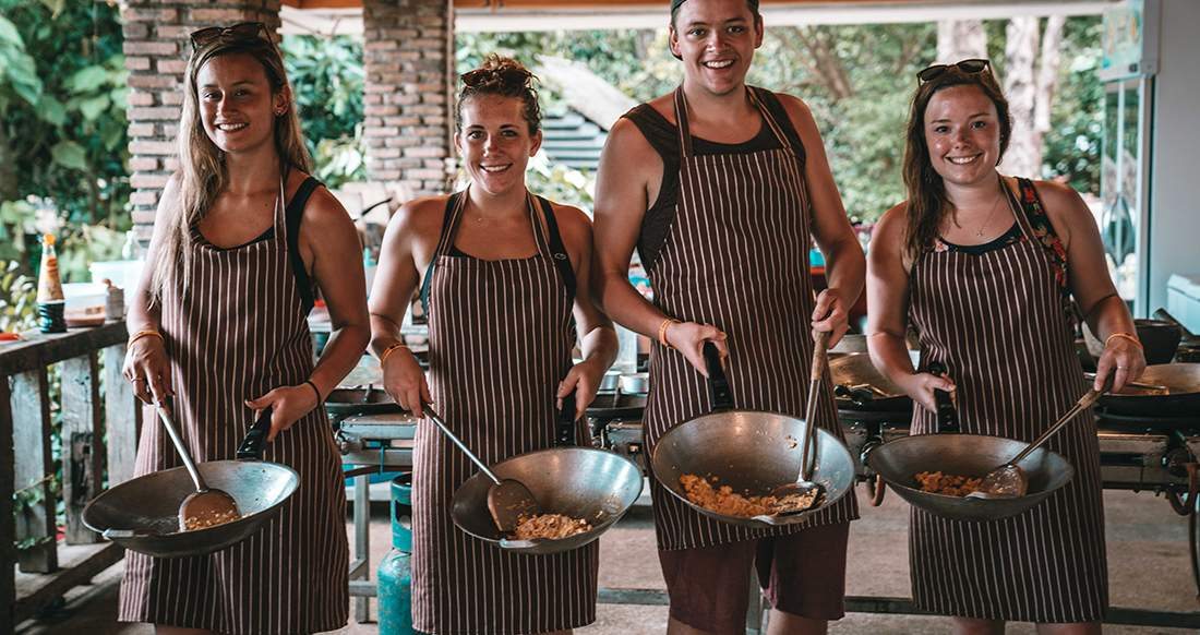 Travelers cooking Thai food at a cooking class in Thailand